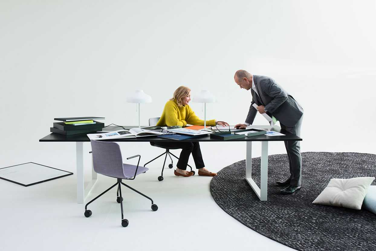 Two people working around a large desk