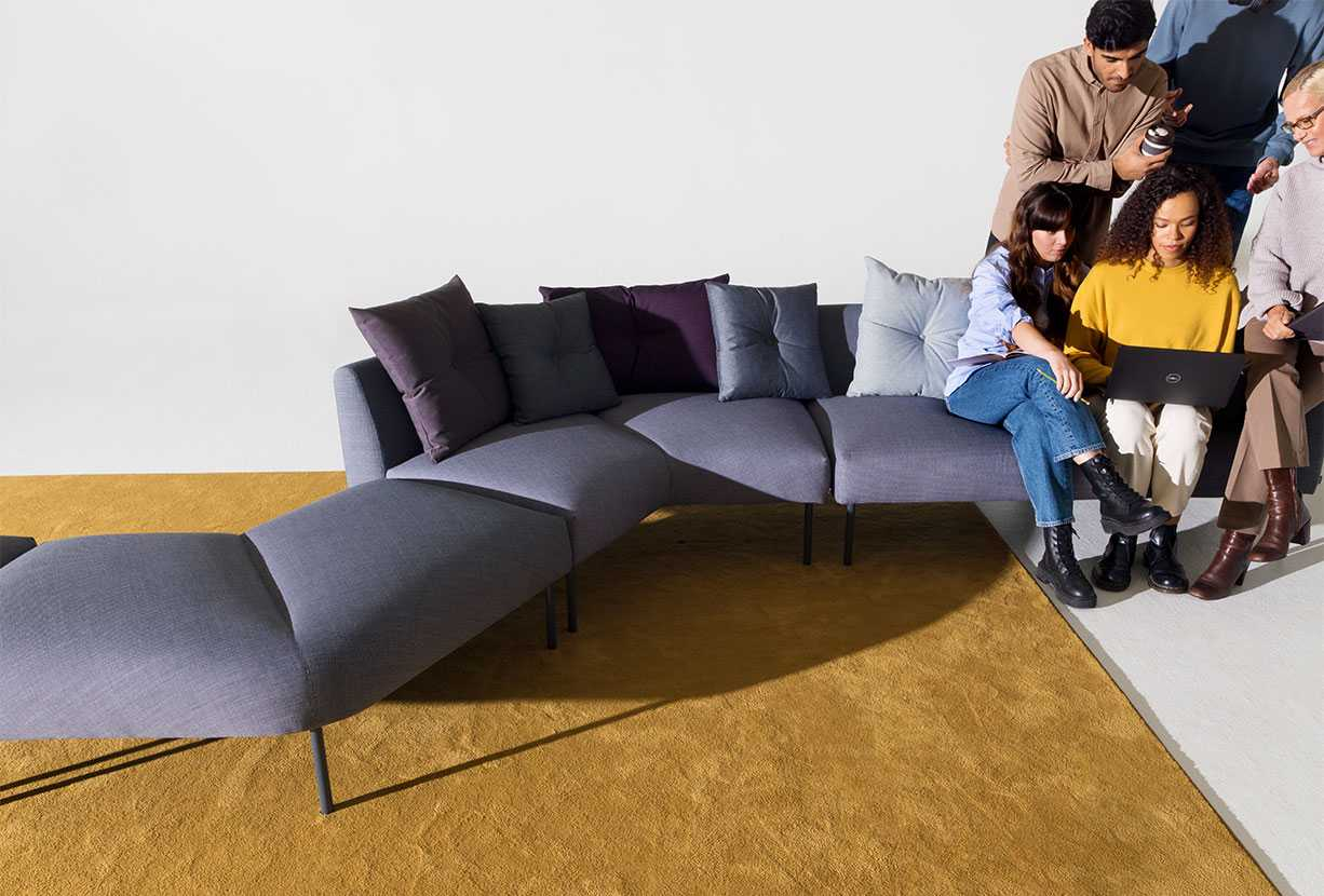 People sitting close to each other on a sofa while the other end is empty