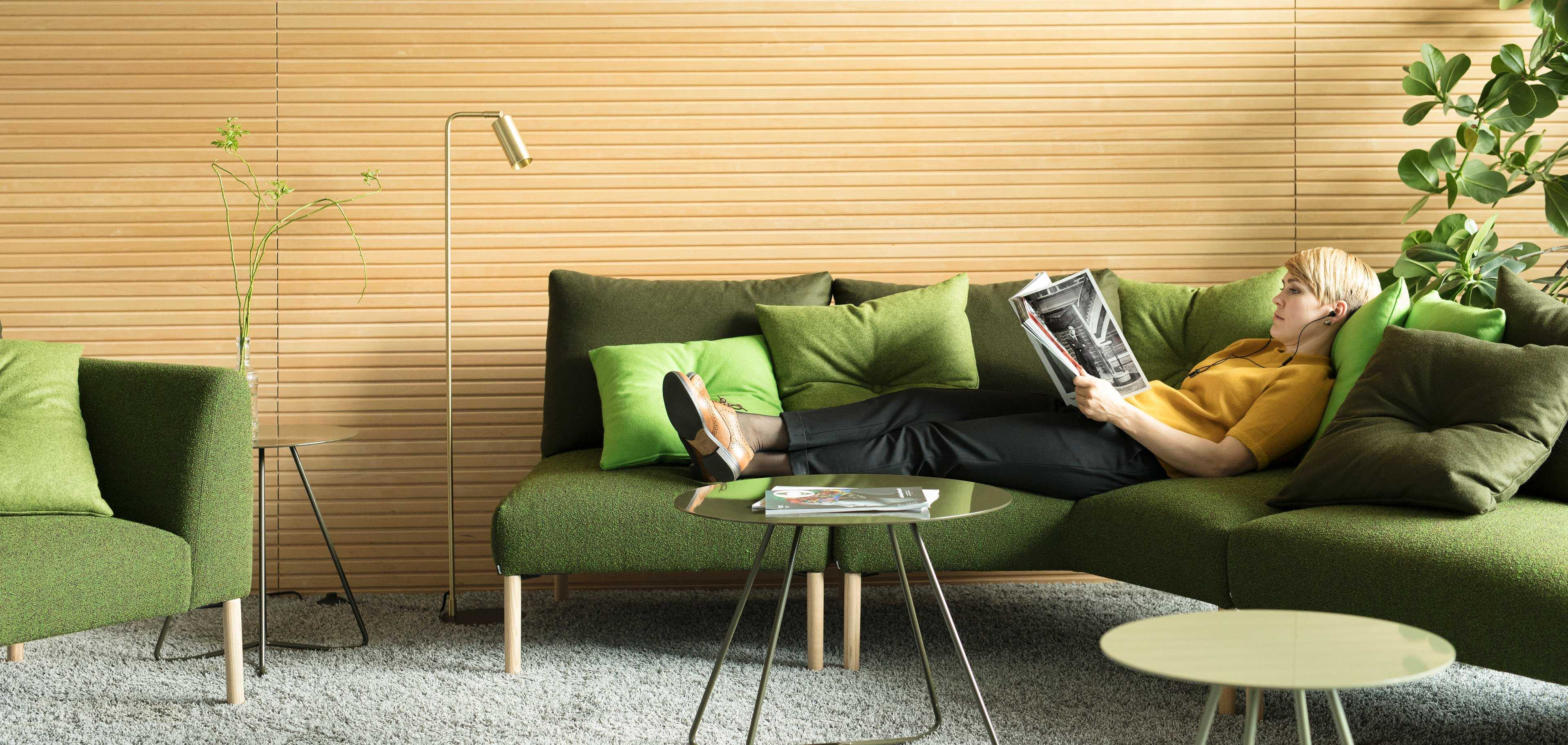 A woman relaxing on a green sofa